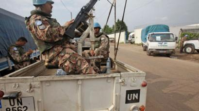 United Nations (UN) peacekeeping force keep guard from a vehicle near a UN warehouse (REUTERS/Thierry Gouegnon)