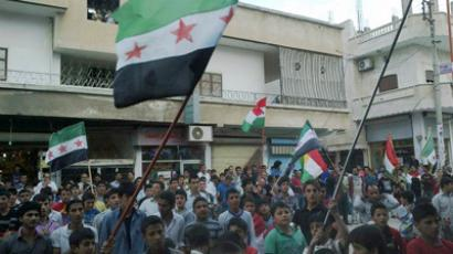 Demonstrators hold Syrian opposition and Kurdish flags during a protest against Syria's President Bashar al-Assad in Qubani, near Aleppo May 21, 2012 (Reuters/Raad Al Fares/Shaam News Network)