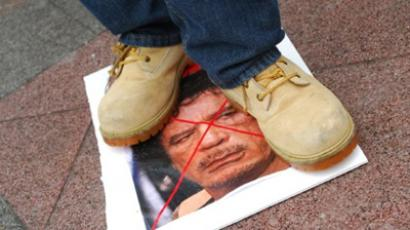 A protester stands on a picture of Muammar Gaddafi (AFP Photo / Mira Oberman)