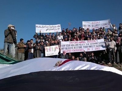 Syrian anti-regime demonstrators holding slogans against Russia's policy at UN Security Council that blocked a resolution calling for an immediate halt to the crackdown in Syria during a rally in the northeastern city of Kafr Nabl on January 20, 2012. (AFP Photo/LCC SYRIA)