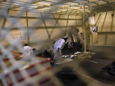 Afghan detainees, seen through a mesh wire fence, prepare for noon prayers inside the Parwan detention facility near Bagram Air Field in Afghanistan  (Image from msn.com)