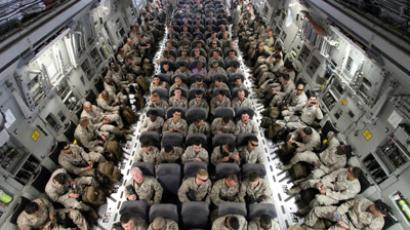 U.S. servicemen sit after boarding a transport plane before leaving for Afghanistan at the U.S. transit center at Manas airport near Bishkek, March 27, 2012 (Reuters/Vladimir Pirogov)