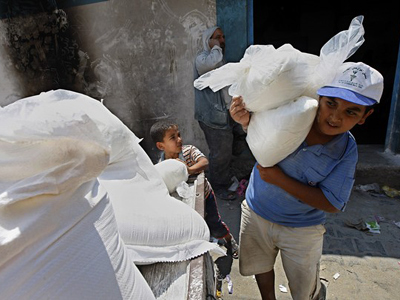 Palestinians receive their monthly food aid in the Rafah refugee camp, southern Gaza Strip, on July 21, 2011