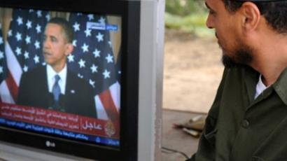 A Libyan rebel fighter listens to US President Barack Obama's speech on TV (AFP Photo / Saeed Khan)