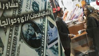 A woman talks to a currency exchange dealer in a shop at northern Tehran (Reuters / Morteza Nikoubazl)