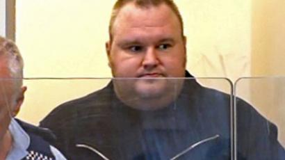 "Megaupload.com, Kim Schmitz, also known as ""Kim Dotcom"", escorted by a policeman as he appears in an Auckland district court in New Zealand on January 20, 2012 (AFP Photo / TV3)"