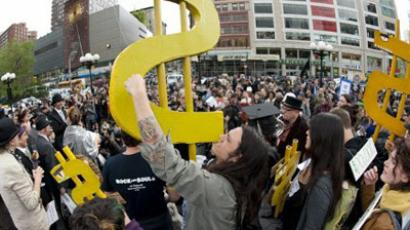A young man holds up a dollar sign during an Occupy Wall Street rally (AFP Photo / Don Emmert)