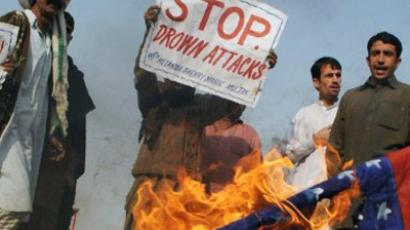 Pakistani protesters gather beside a burning US flag during a demonstration in Multan on January 11, 2012 against the US drone attacks in Pakistani tribal areas (AFP Photo / S.S. Mirza)