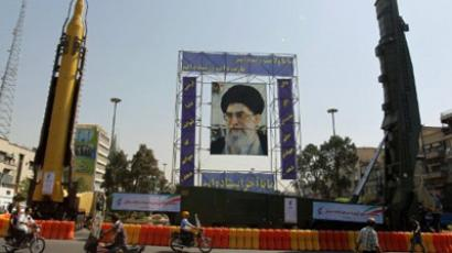 A huge picture of Iranian supreme leader Ayatollah Ali Khamenei is erected between a Sajjil (R) and Qadr-F (L) missiles (AFP Photo / ATTA KENARE)
