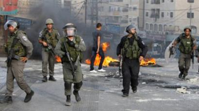 Israeli soldiers walk past burning tyres during clashes with Palestinian youths in the Shuafat refugee camp on the outskirts of Jerusalem on September 23 (AFP Photo / AHMAD GHARABLI)