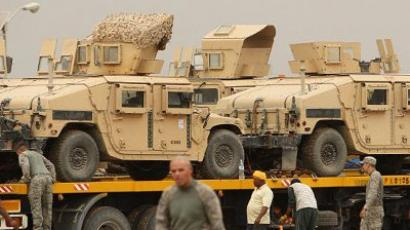 US soldiers secure vehicles mounted on trucks at the military base of Camp Kalsu in the town of Iskandiriyah in Iraq's Babel province, 50 kilometres (30 miles) south of Baghdad, on October 26, 2011.  (AFP Photo / Ali Al Saadi)
