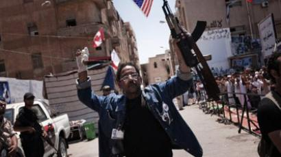 Benghazi: A Libyan man raises his AK47 gun, with an US flag, ahead of the Friday noon prayer on June 17, 2011, in the Libyan rebel-stronghold city of Benghazi. (AFP Photo / Gianluigi Guercia)