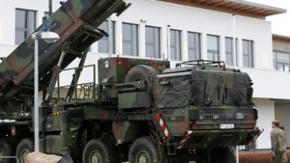 A soldier of the Air Defence Missile Squadron 2 walk past a Patriot missile launcher in the background in Bad Suelze, northern Germany on December 4, 2012. (AFP Photo/Bernd Wustneck)