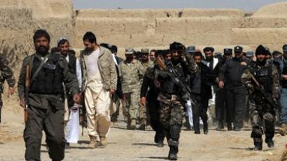 An Afghan delegation walk swith locals after a gathering for a memorial ceremony at Mohammad mosque in Alokozai village of Pajwai district in Kandahar province on March 13, 2012 (AFP Photo / Jangir)