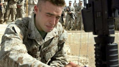 A marine paying his last respects to his close friend during a memorial service that was held at Camp Baharia, in Iraq (AFP Photo / BRIAN REIMERS)