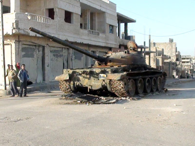Syrians stand next to a destroyed and abandoned army tank on March 10, 2012, in the Syrian town of Rastan (AFP Photo/Str)