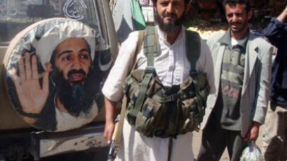 A fighter is seen standing in front of an image of Osama bin Laden, the late head of al-Qaeda, in the town of Rada, 130 kilometres (85 miles) southeast of the capital Sanaa, on January 21, 2012 (AFP Photo/Str)