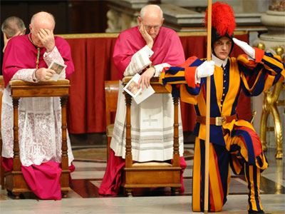 A Swiss guard stands guards whille ecclesiasts pray during the celebration of Vespers on the feast of the Presentation of the Lord on January 2, 2012 at St Peter's basilica at the Vatican.(AFP Photo / Vincenzo Pinto)