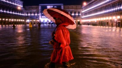"A man walks on the flooded Saint Mark's square during an ""acqua alta"" ('high waters') flooding.(AFP Photo / Olivier Morin)"