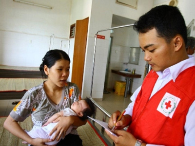 A Red Cross volunteer talks to Hoang Thi Kim Phung, whose two-and-a-half -month-old son was admitted to hospital in Long An, Vietnam, with symptoms of hand, foot and mouth disease (Quang Tuan / Vietnam Red Cross)