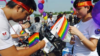 Cyclists decorate their bicycles with balloons and rainbow flags prepare to take part in Vietnam's first ever gay pride parade on a road in Hanoi on August 5, 2012 (AFP Photo / Hoang Dinh Nam)