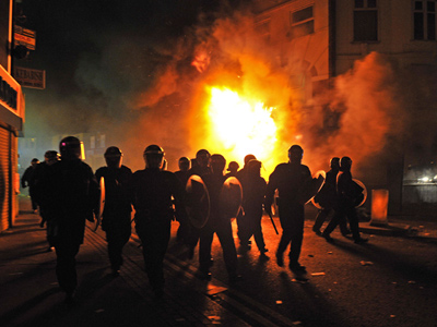 British riot police arrive in front of a burning building in Croydon, South London on August 8, 2011 (AFP Photo)