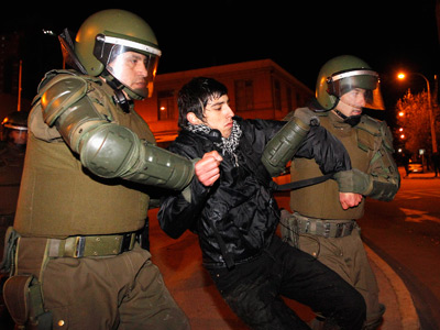 A demonstrator is detained by riot police officers during a protest in Valparaiso city, about 121 km (75 miles) northwest of Santiago, July 25, 2012. (Reuters / Eliseo Fernandez)