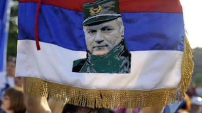 A protestor holds a falg with a picture of Bosnian Serb war crimes suspect Ratko Mladic as she attends a demonstration in front of Serbian Parliament on May 29, 2011 in Belgrade, called by ultra-nationalists against Mladic's arrest lats May 26 (AFP PHOTO / ANDREJ ISAKOVIC)