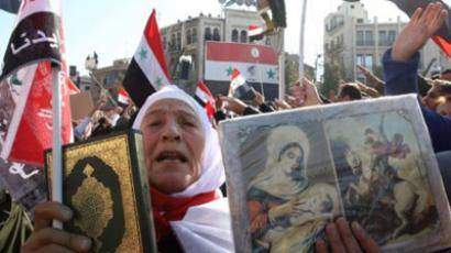 A Syrian woman holds up a copy of the Muslim holy Quran next to a Christian icons, during a demonstration in the capital Damascus (AFP Photo / LOUAI BESHARA)