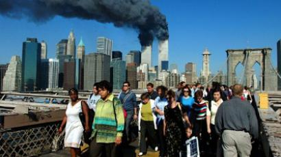 Pedestrians walk across the Brooklyn Bridge away from the burning World Trade towers before their collapse 11 September, 2001 (AFP Photo / Henny Ray ABRAMS)