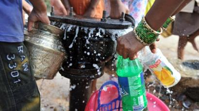 Indian women fill containers with drinking water from a leaking water pipe line (AFP Photo / Noah Seelam)