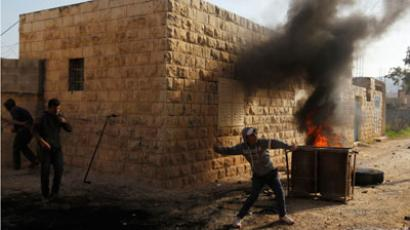 A Palestinian protester throws a stone near burning tyres during clashes with Israeli security officers in the West Bank village of Tamoun, near the West Bank city of Jenin.(Reuters / Ammar Awad)