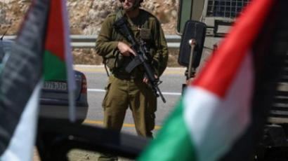 An Israeli soldier keeps watch near Palestinian flags in the Jewish settlement of Halamish after Palestinian activists started a surveillance campaign throughout the Israeli-occupied West Bank to monitor settler's illegal activities on September 19, 2011 (AFP Photo / ABBAS MOMANI)