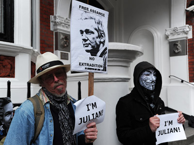 "A man holds a ""Free Assange - No Extradition"" sign alongside a protester wearing a Guy Fawkes mask and holding a sign reading ""I'm Julian"" as they demonstrate outside the Ecuadorian embassy in London, on June 23, 2012, where WikiLeaks founder Julian Assange is seeking political asylum (AFP Photo/Carl Court)"