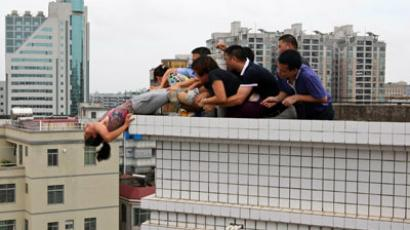 Rescuers and relatives stop a woman from committing suicide by jumping off a building in Zhanjiang, Guangdong province (Reuters / CDIC)