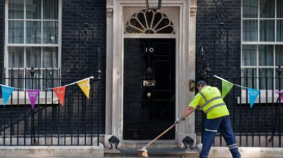 A road cleaner sweeps outside no 10 Downing Street in central London.(AFP Photo / Will Oliver)