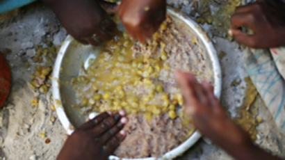 Internally displaced children eat a food ration at a food distribution point (AFP Photo / Mohamed Dahir)