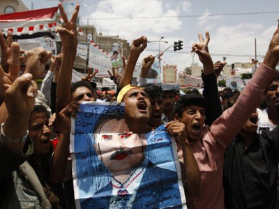 Yemeni anti-government protesters shout slogans during a demonstration calling for the ouster of President Ali Abdullah Saleh (defaced poster) in Sanaa on June 4, 2011 (AFP Photo / Ahmad Gharabli)
