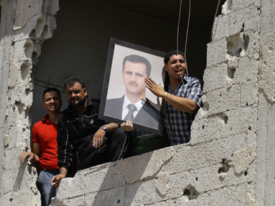 Syrians in a damaged building hold up a portrait of their President Bashar al-Assad (AFP Photo / Louai Beshara)