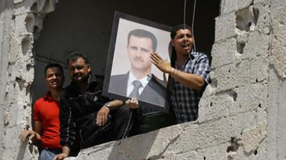 Syrians in a damaged building hold up a portrait of their President Bashar al-Assad (AFP Photo / Louai Beshara)