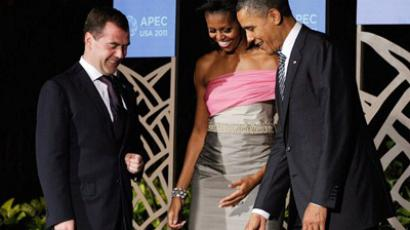 U.S. President Barack Obama points to a marker on the floor as he and first lady Michelle Obama welcome Russian President Dmitry Medvedev to the Asia-Pacific Economic Cooperation (APEC) summit dinner on November 12, 2011 in Waikiki, Hawaii (AFP Photo / Kevork Djansezian)