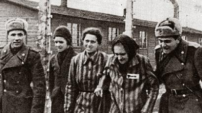 Two Soviet soldiers escort prisoners on the day of their liberation, January 27, 1945. Auschwitz, Poland