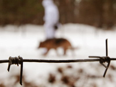 A Belarussian border guard walks with a dog near the Belarus-Poland border. (REUTERS/Vasily Fedosenko)