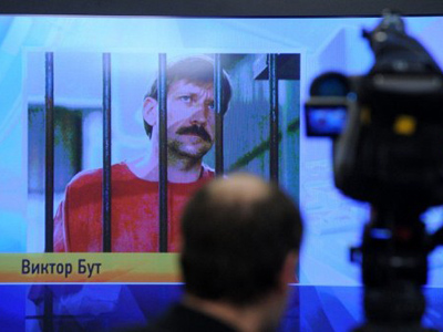 journalist stands near a screen displaying convicted Russian arms smuggler Viktor Bout in Moscow, on April 12, 2012, during a teleconference with Bout from his US prison (AFP Photo/Kirill Kudryavtsev)