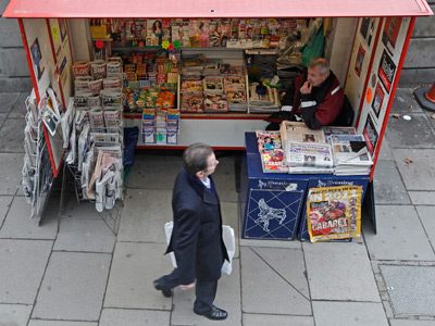A man passes a newsagents stand displaying newspapers and magazines central London (Reuters / Luke MacGregor)
