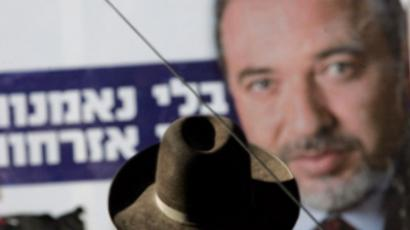 Israeli Ultra Orthodox man in front of an elections campaign poster of Avigdor Lieberman, leader of the far-right party (AFP Photo / Gali Tibbon )