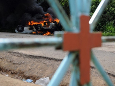 Members of the Resistance Movement against the coup d'etat detected the two DNIC policemen and burnt their car outside the cemetery. AFP Photo/Yuri Cortez