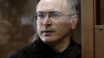 Mikhail Khodorkovsky stands behind a glass wall.  ( AFP Photo / Alexey Sazanov )