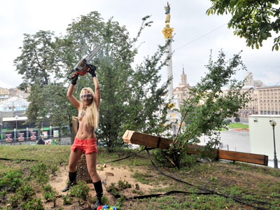 An activist of the Ukrainian feminist group Femen raises a chainsaw after cutting down a cross, erected to the memory of victims of the political repression in Kiev.(AFP Photo / Genya Savilov)