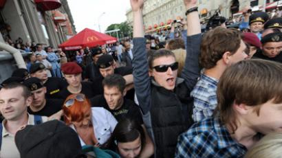 "Belarussian police officers (background) cordon off the area of a flashmob, called ""Revolution Via Social Network"" in the center of Minsk on June 15, 2011 (AFP Photo / Viktor Drachev)"